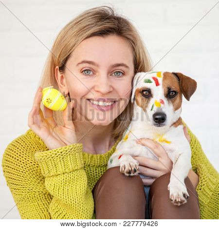 Woman and dog color Easter eggs. Female with pet