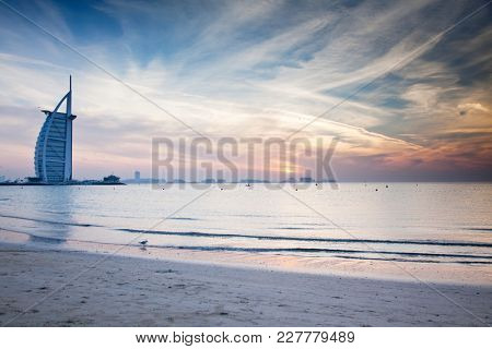DUBAI, UAE - FEBRUARY 2018 :The world's first seven stars luxury hotel Burj Al Arab at sunset seen from Jumeirah public beach in Dubai, United Arab Emirates