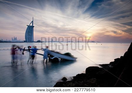 DUBAI, UAE - FEBRUARY 2018 :The world's first seven stars luxury hotel Burj Al Arab at sunset seen from Jumeirah public beach. People prepare a boat to go out fishing in the sea.