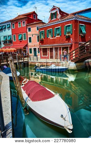 Burano, Italy - May 21, 2017: View Of Buildings And Places To Eat In Front Of A Canal And Parked Boa