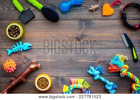 Pet Accessories. Toys Near Bowls With Animal Feed, Collar On Dark Wooden Background Top View.