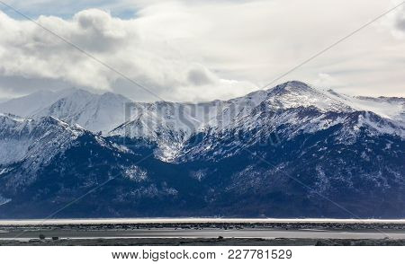 Snowy Mountains Across The Sound In The Winter. The Tide Is Out
