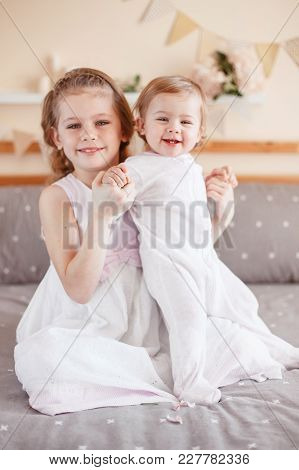 Portrait Of Cute Adorable White Caucasian Girl Holding Little Sister Baby On Laps Knees. Smiling Chi