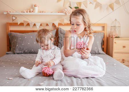 Two Cute Adorable White Caucasian Girsl Holding Pink Cupcakes Celebrating Birthday. Smiling Children