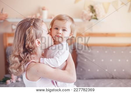 Two Cute Adorable White Caucasian Girsl Sisters Kissing. Children Sitting Together On Bed In Bedroom