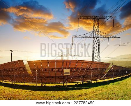 Electricity Transmission Pylon With Solar Panel Against The Sunset.