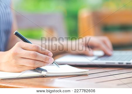 Business Woman Hand Writing On Notepad With A Pen And Working Laptop Computer In The Garden In Front