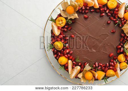 Tangerine Homemade Cake Decorated With Chocolate Icing And Mandarines, Pomegranate, White Cream. Top