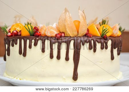 Whole Tangerine White Cake With Sizalis Flowers And Chocolate Icing And Fruts Decoration. Homemade D