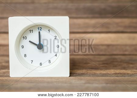 Closeup White Clock Show Ten O'clock On Blurred Brown Wood Board Background