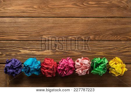 Set Of Multiple Colorful Crampled Paper Ball Placed In Line On Wooden Table As Means Of Searching Of