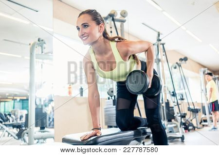 Low-angle view portrait of a beautiful fit woman smiling while exercising one arm dumbbell row for back muscles in a modern fitness club