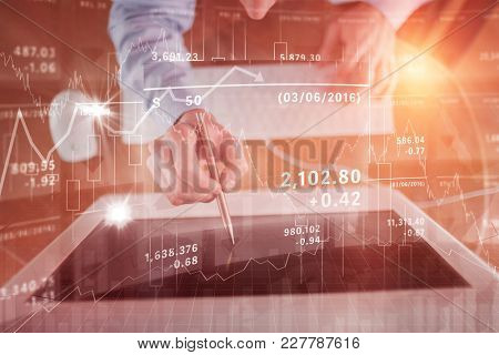 Businessman pointing to screen with pen against stocks and shares