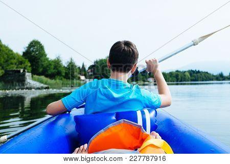 12 Year Old Boy Lying In Canoe On Lake Monate