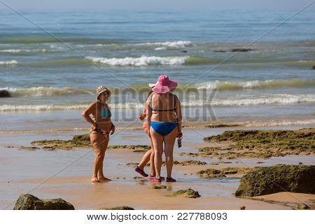 ALBUFEIRA, PORTUGAL - AUGUST 22, 2017: People at the famous beach of Olhos de Agua in Albufeira. This beach is a part of famous tourist region of Algarve.