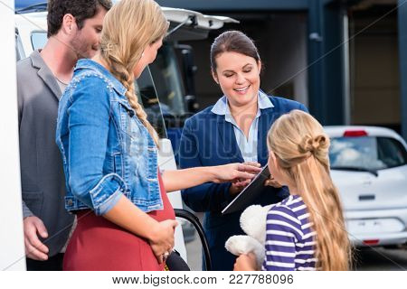 Family being advised by salesperson in car dealership buying car