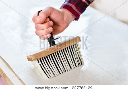 Close-up of the hand of a man holding a synthetic brush with plastic handle while applying paste to the surface of the wallpaper sheet