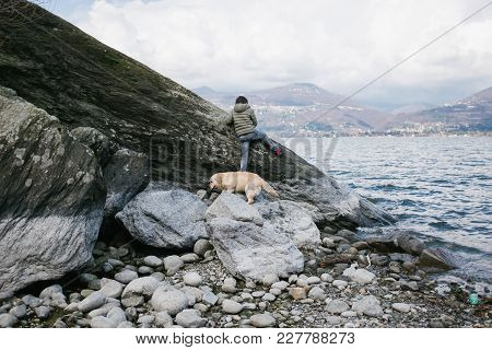 12 Year Old Boy With His Dog Playing Near A Boulder