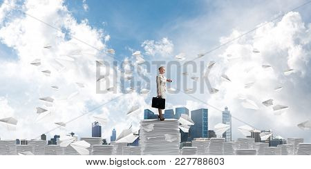 Confident Business Woman In Suit Standing Among Flying Paper Planes With Cloudly Skyscape On Backgro