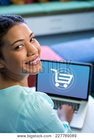 Digital composite of Woman using Laptop with Shopping trolley icon