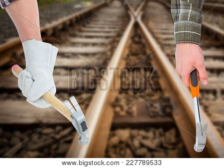 Digital composite of hands with hammers in the railroad tracks