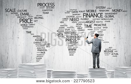 Businessman In Suit Standing On Pile Of Documents With Speaker In Hand With Business-related Terms I