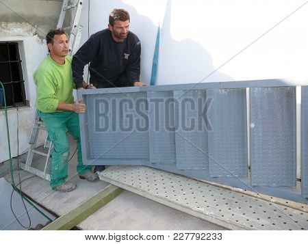 Alora, Spain - December 15, 2011: Men Lifting Steel Staircase In Village House In Andalusia