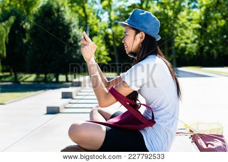 Young Asian woman making selfie pictures outdoors in the park in a sunny day