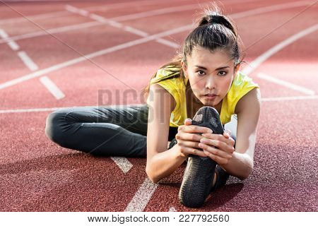 woman athlete stretching on racing track before sprint