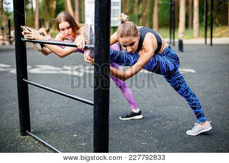 Two Young Sporty Girl Doing Stretching Exercises Outdoors