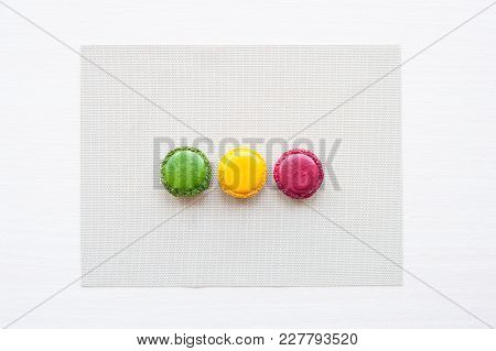 Three Red, Yellow And Green Round French Macaron Cookies On The Table