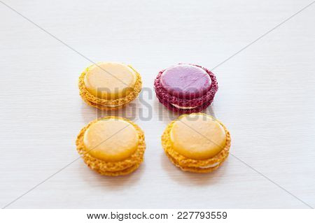 Four Colorful Round French Macaron Cookies On The Table