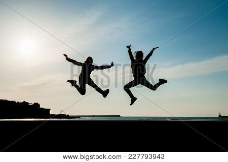 Two Happy Jumping Teen Girls On Blue Sky Background At Sunset