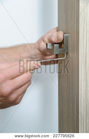 A Man Is Installing A Hook For Clothes. He Is Using A Hex Key To Fix The Bracket Of The Hook.