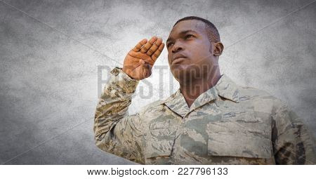 Digital composite of Soldier saluting against white wall with grunge overlay