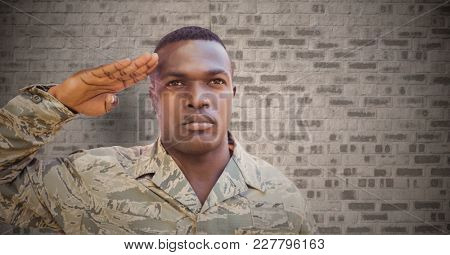 Digital composite of Soldier saluting against brown brick wall