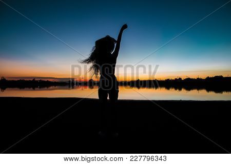 Girl Silhouette In Front Of A Lake After The Sunset, Orange And Blue Sky In The Background.