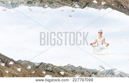 Young Woman Keeping Eyes Closed And Looking Concentrated While Meditating On Cloud Among Flying Pape