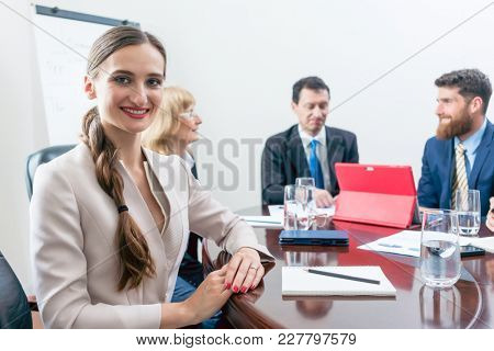 Portrait of a beautiful business woman looking at camera with a can-do attitude, while sitting down at a round table during a decision-making meeting with the board of directors