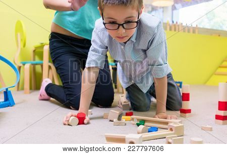 Cute pre-school boy wearing eyeglasses while playing with wooden toys during supervised free playtime at the kindergarten