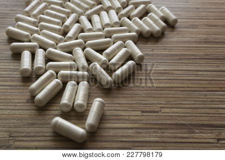 Pile Of Many Oval White Drug Pills Laying In A Pile On Wooden Table. Pile Of White Pills Or Tablets