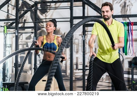 People doing functional training with battle rope in gym