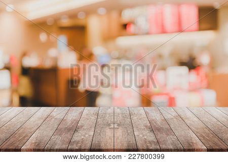 Wood Table Top And Blurred Bokeh Cafe And Coffee Shop Interior Background With Vintage Filter - Can