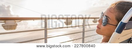 Cruise ship vacation travel woman relaxing panoramic crop. Banner of girl with sunglasses lying down sun tanning on balcony. Suntan carefree. Horizontal copy space. Caribbean travel.