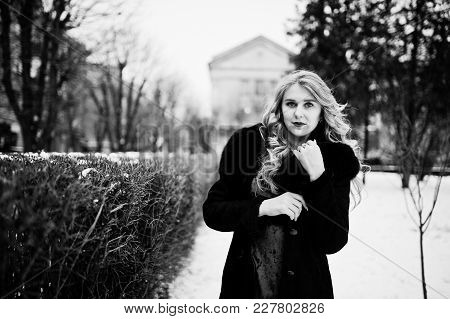 Elegance Blonde Girl In Red Evening Dress And Fur Coat At Streets Of City In Winter Day.