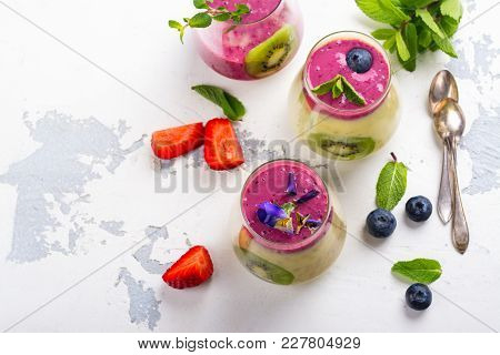 Colorful Detox Layered Smoothie With Natural Edible Flowers, Berries And Mint On White Background. C