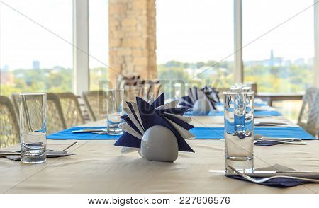 Empty Half-served Banquet Table In Restaurant With Napkins, Glasses, Forks, Knives, Shallow Dof View