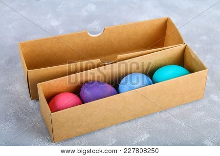 Colored Easter Eggs In A Gift Box On A Gray Concrete Background