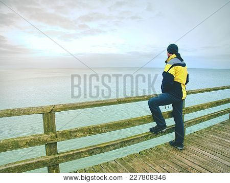 Man Thinking. Tourist  In Warm Clothes On Sea Mole At Wooden  Handrail. Autumn Misty Day. Tourist On
