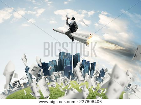 Conceptual Image Of Young Businessman In Suit Flying On Rocket Among Flying Papers With Cityscape An